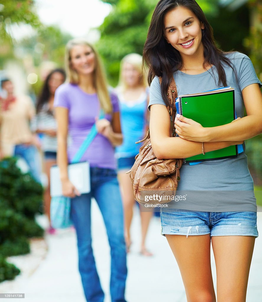 Beautiful, young woman standing in the campus and smiling' : Stock Photo