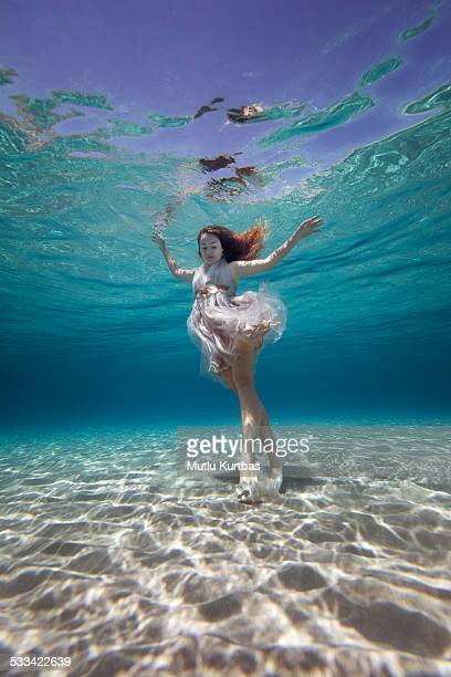 Beautiful young woman standing underwater