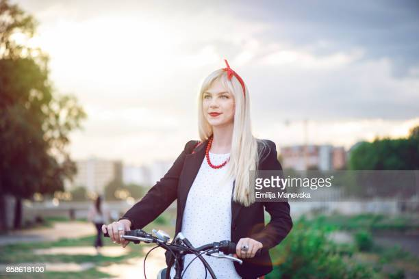 A beautiful young woman standing with her vintage bicycle