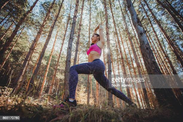 Beautiful young woman stretching in nature