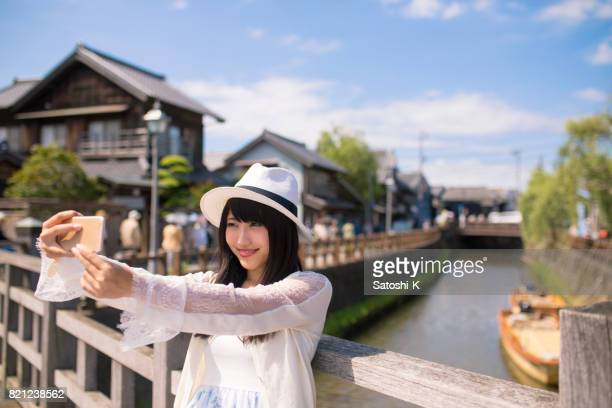 Schöne junge Frau, die unter Piture mit Smartphone