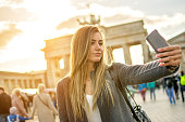 Beautiful young woman taking selfie photo in front of Brandenburger Tor in Berlin at sunset.