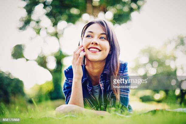 Beautiful young woman talking on smart phone in park