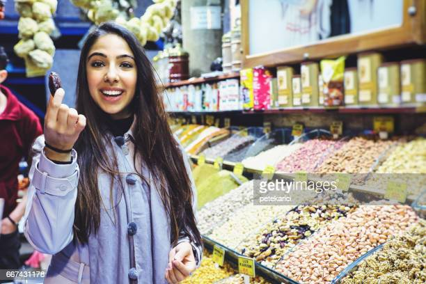Beautiful young woman tastes dates fruit in Grand Bazaar, Istanbul, Turkey