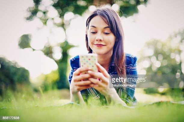 Beautiful young woman text messaging on smart phone in park