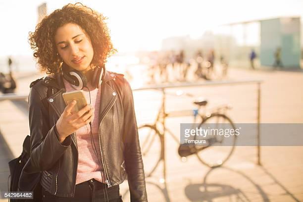 Bellissima ragazza messaggi di testo con suo smartphone.
