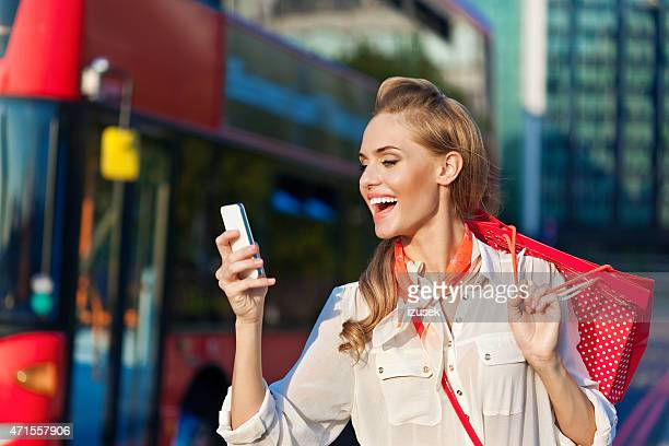 Beautiful young woman texting on smart phone in London