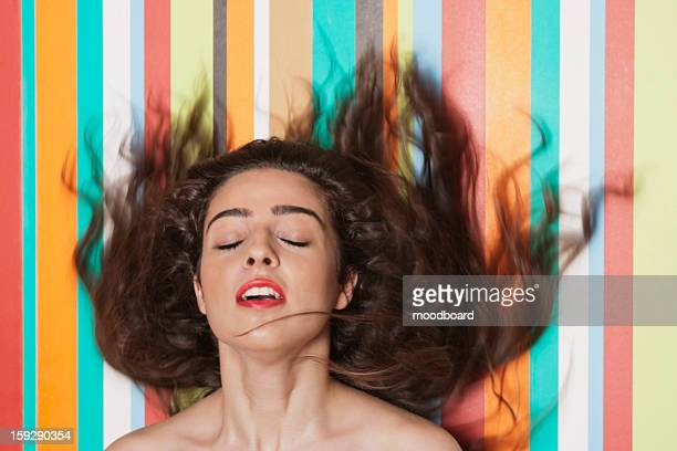 Beautiful young woman tossing hair against colorful striped background