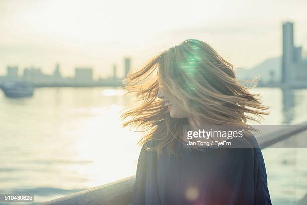 Beautiful young woman tossing hair against the river