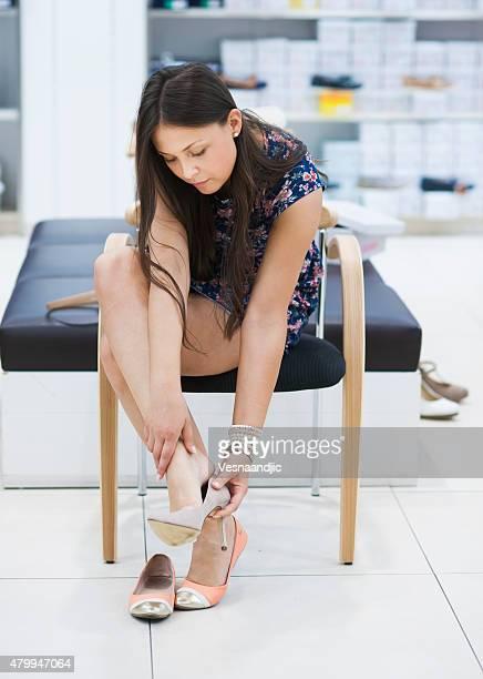 Bela jovem tenta sobre sapatos na loja de calçado