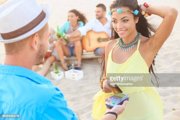 Beautiful young woman using credit card for contactless payment on beach