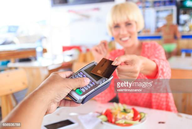 Beautiful young woman using credit card for contactless payment