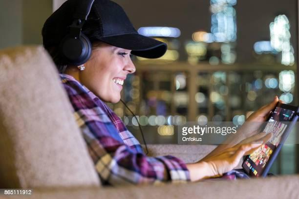 Schöne junge Frau, die mit Digital-Tablette zu Hause