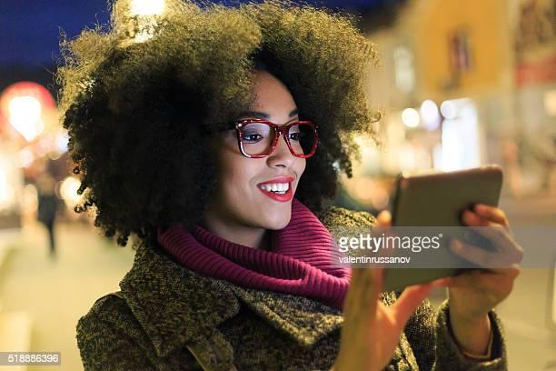 Schöne Junge Frau mit Digitaltablett bei Nacht