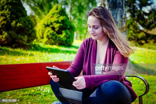 Beautiful young woman using digital tablet outdoors