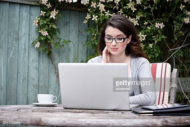 Beautiful young woman using laptop in garden
