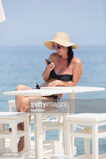Beautiful young woman using phone on tropical beach : Stock Photo