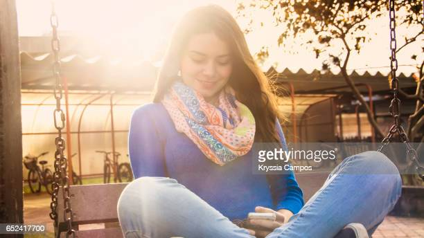 Beautiful young woman using smart phone at sunset