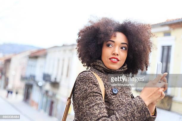 Beautiful young woman using smart phone on street