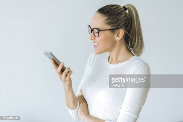 Beautiful young woman using smartphone at the office
