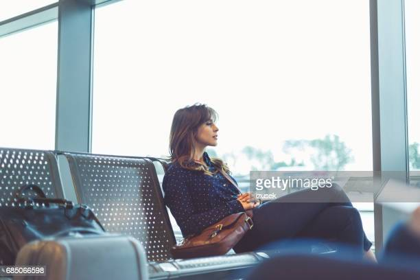 Beautiful young woman waiting her flight at airport