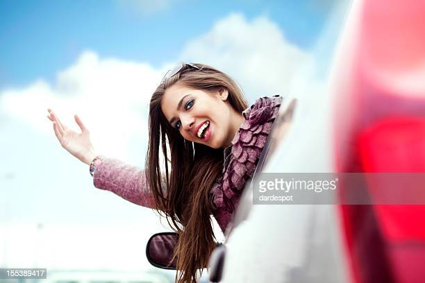 A beautiful young woman waving from her car