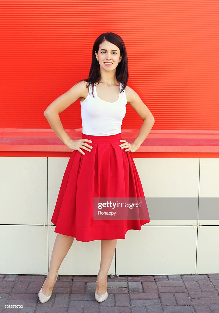 Beautiful young woman wearing a red skirt over colorful background : Stockfoto