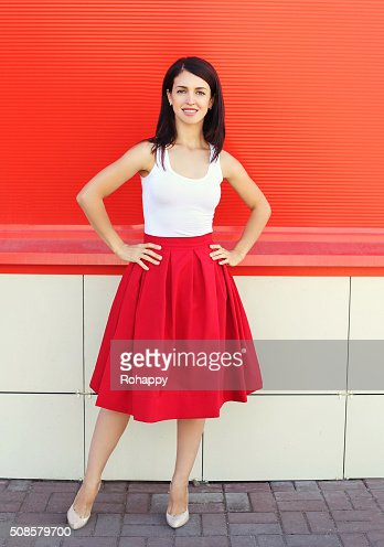 Beautiful young woman wearing a red skirt over colorful background : Stock Photo
