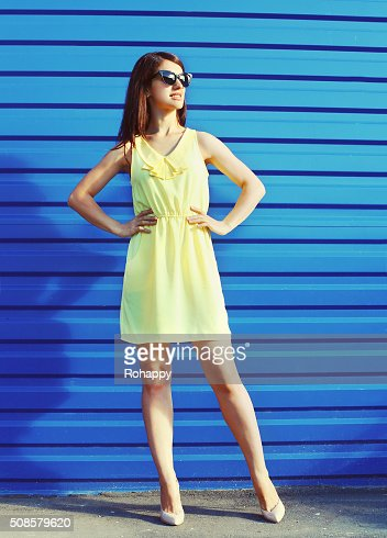 Beautiful young woman wearing a sunglasses and yellow dress : Stockfoto