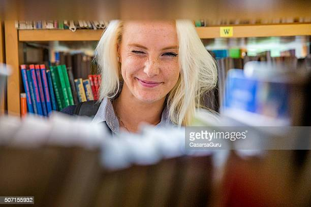 Beautiful Young Woman Winking in Library