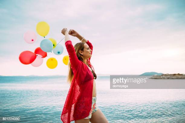 Beautiful young woman with balloons having fun at the beach