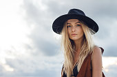 Close up of beautiful young blonde woman with black hat. Wearing brown vest. Her long messy hair looks amazing.