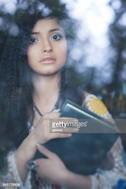 Beautiful young woman with book behind glass window.