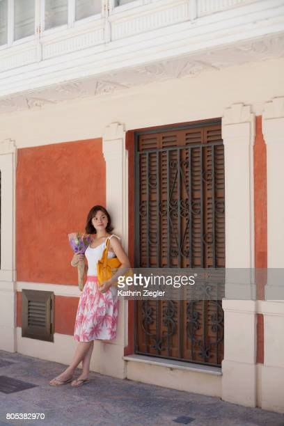 Beautiful young woman with bouquet leaning against wall, Palma de Mallorca