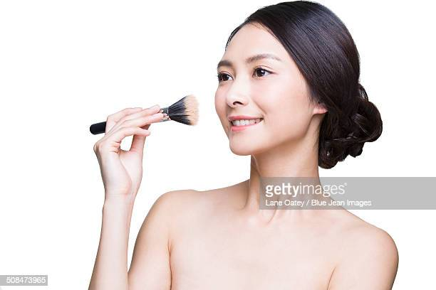 Beautiful young woman with cosmetic brush