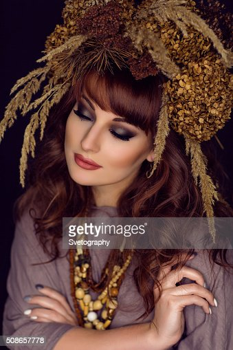 Beautiful young woman with dry flowers on head : Stock Photo