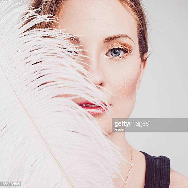 Beautiful young woman with elegant make-up and feather