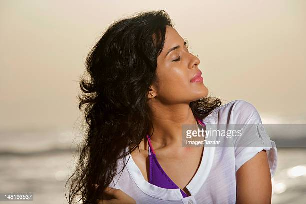 Beautiful young woman with eyes closed on beach