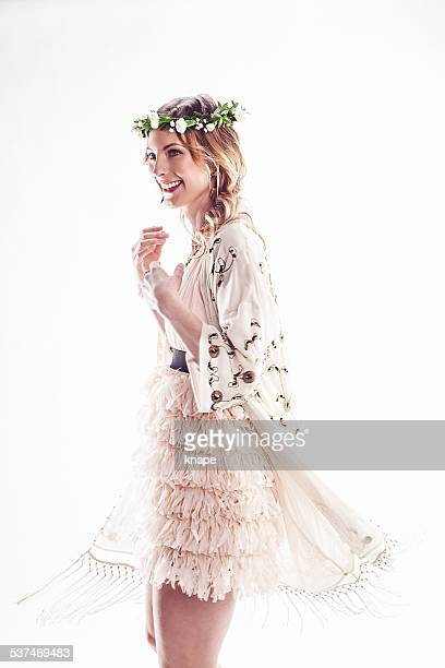 Beautiful young woman with flower wreath in her hair dancing