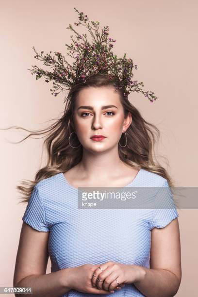 Beautiful young woman with flowers as a crown