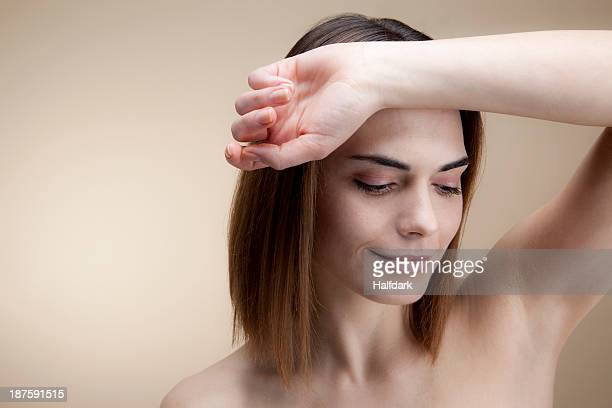 A beautiful young woman with her forearm resting on her forehead looking down serenely