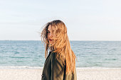 Beautiful young woman with long brown hair turns and looks at camera on the beach
