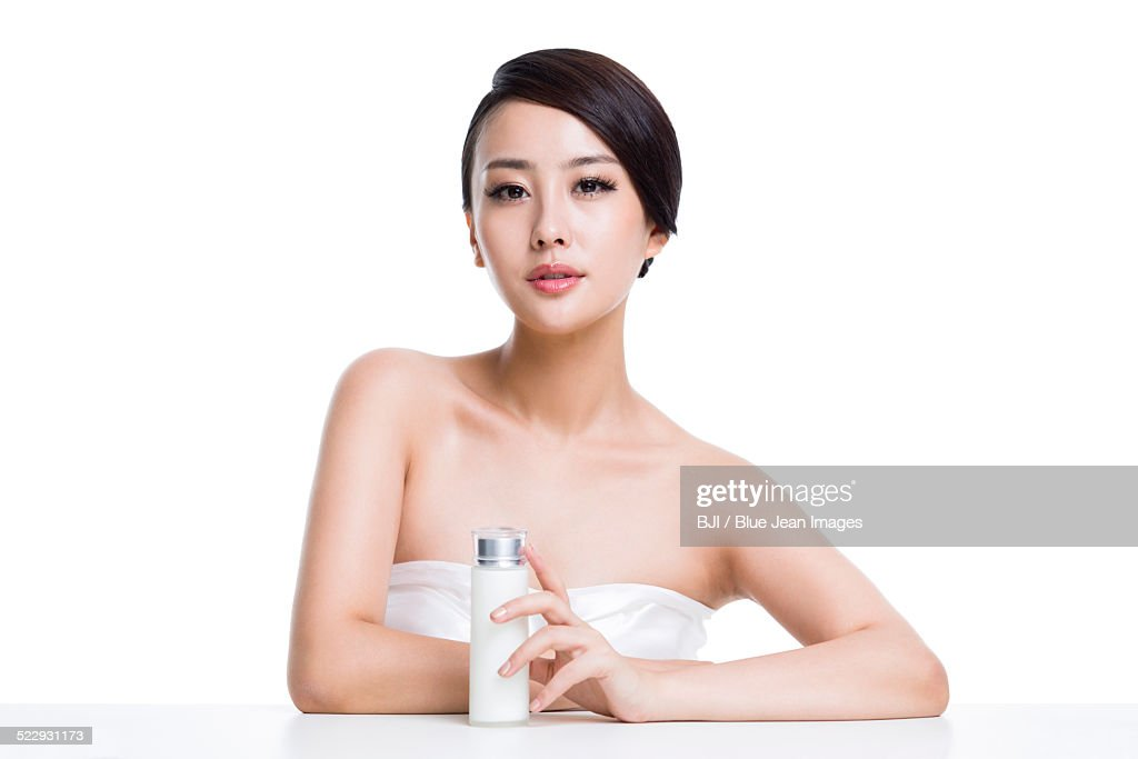 Beautiful young woman with lotion : Stock Photo