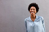 Portrait of beautiful young african american woman with lovely smile on her face standing against a gray wall