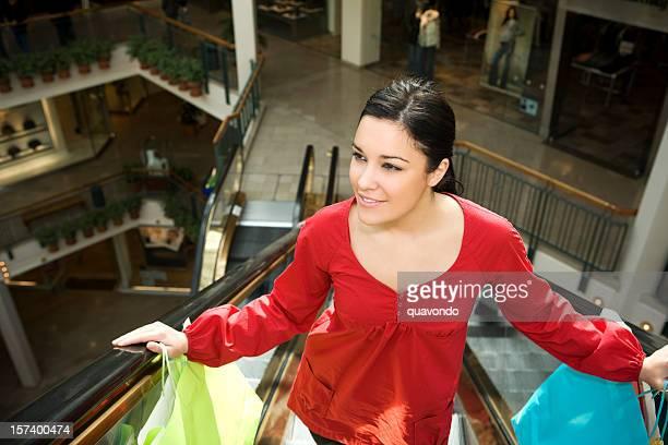 Schöne Junge Frau mit Einkaufstüten in Einkaufszentrum Rolltreppen