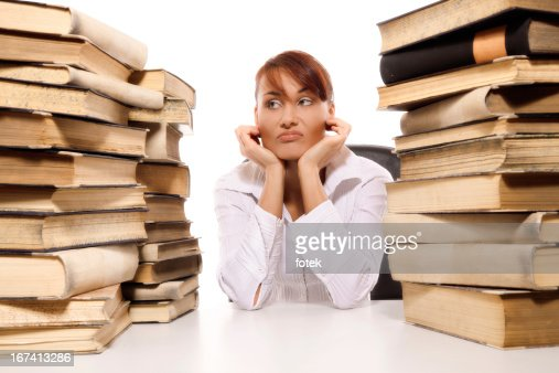 Beautiful young woman with stack of books : Stock Photo