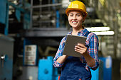 Portrait of female factory worker using digital tablet and smiling, looking at camera posing in modern workshop