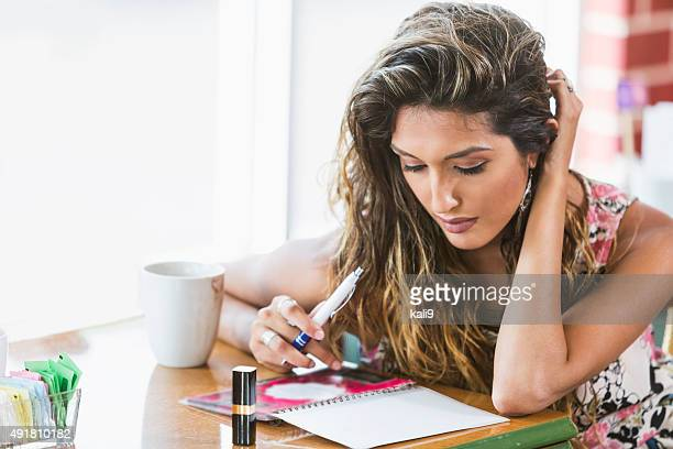 Beautiful young woman writing in a journal