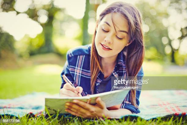 Beautiful young woman writing in diary while lying at park