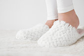 Beautiful, young woman's legs with white, soft, warm slippers on the fluffy mat in the  bedroom after waking up in the morning. Rest at home in day off.